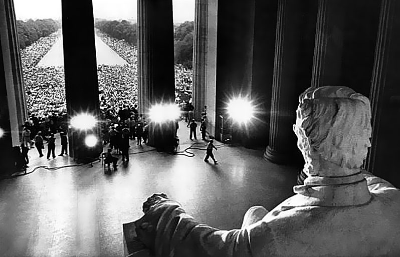 glack and white photo of the crowd at MLK I have a dream speech shot from behind the statue of Abraham Lincoln's head in the Lincoln Memorial