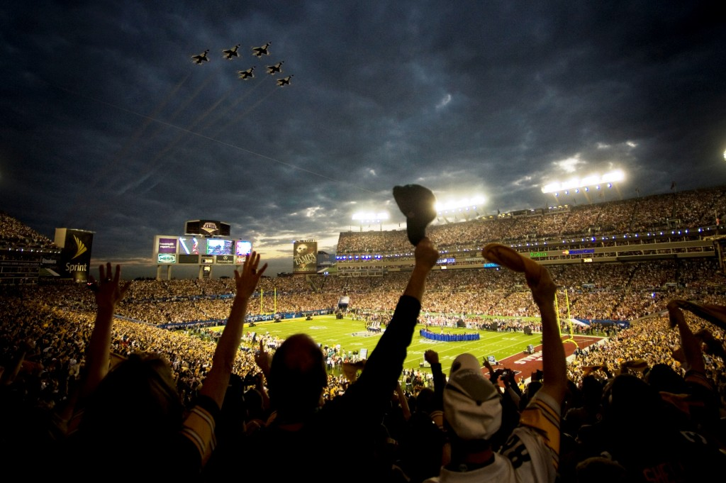 scene at an NFL game with military jets flying over the field and enthusiastic crowd