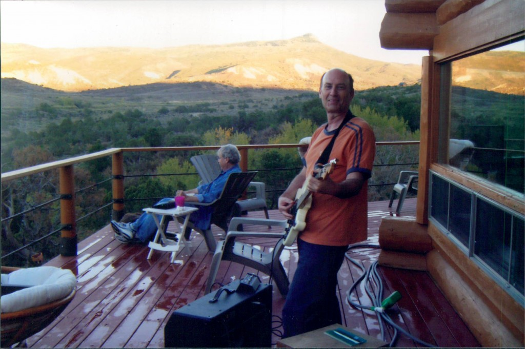 Lory Kohn playing a stratocaster on the deck outside Paonia, Colorado