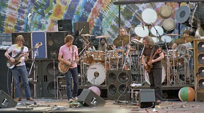 The Grateful Dead jamming in front of huge tie die