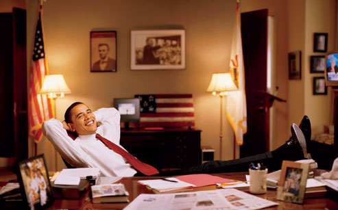 Obama relaxing in his office with pictures of Lincoln and MLK in the background