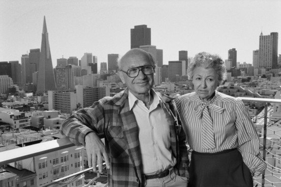 Economist Milton Friedman and his wife Rose pose on a balcony overlooking San Francisco