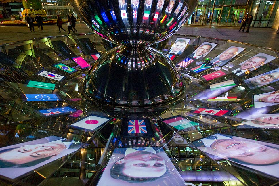 Seoul, Korea — The faces of G-20 leaders are projected onto a mirrored revolving sculpture.