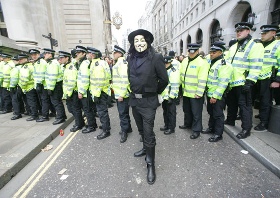 Man in V mask in front of police at G20 economic summit London