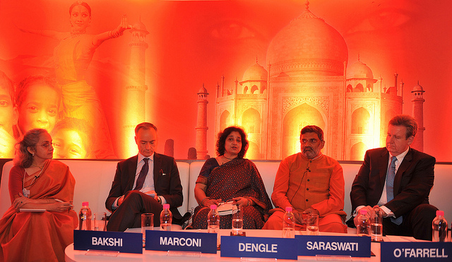 an economics summit in India with a background of fiery red lighting the taj mahal and tantric symbology