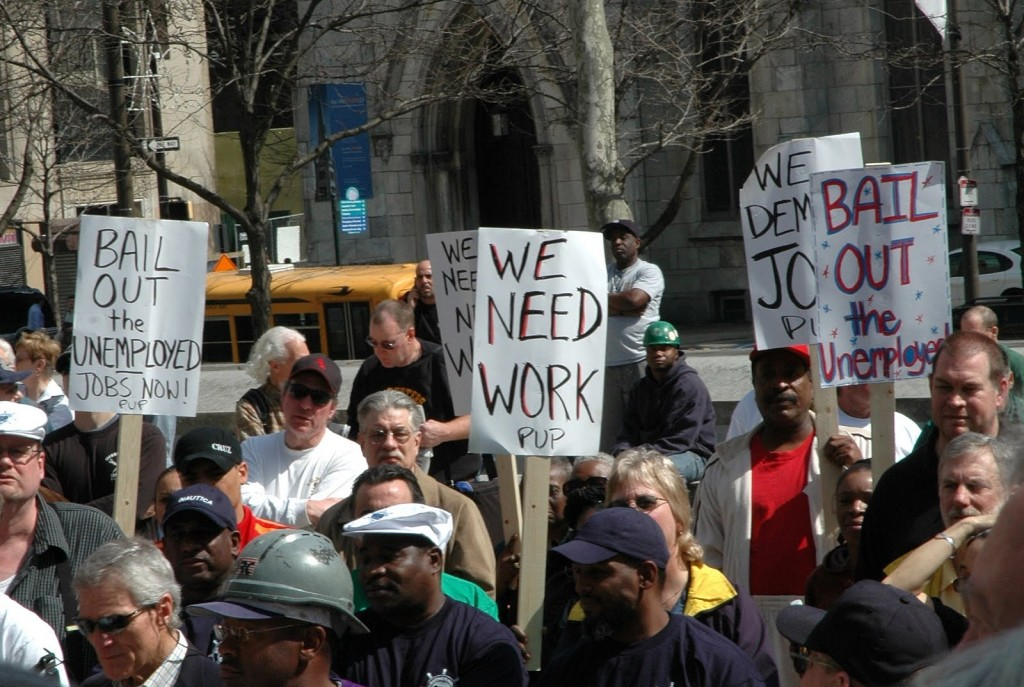 "Unemployed protesters carry signs saying ""we need work"""