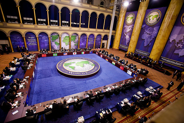 Lavish World economic summit economists sitting around huge table deciding the world's fate